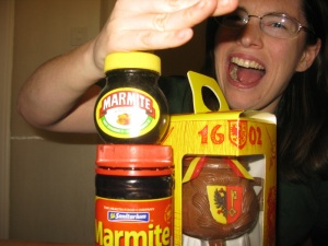 Fake Genevan karate-chopping two jars of different kinds of Marmite, while a Marmite de l'Escalade sits unharmed behind them.