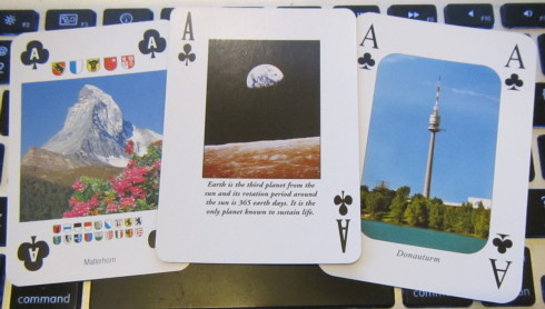 Aces of clubs showing the Matterhorn in Switzerland, the Donauturm in Vienna, and Earthrise over the Moon, with the caption 'Earth is the third planet from the sun and its rotation period around the sun is 365 earth days. It is the only planet known to support life.'