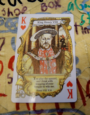 King of Hearts with the Shakespearean insult, 'You play the spaniel, and think with wagging your tongue to win me' against a backdrop of a Worm Quartet Songs of the Maniacs poster