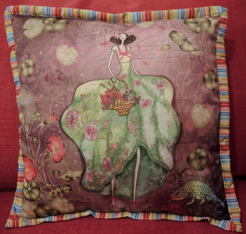 A photo of a cushion which has a picture of a one-eyed woman and a chameleon on it.