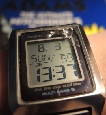 A Casio digital watch displaying Sunday, 3 August, at 13:37:59 daylight savings time, set against a backdrop of The Ultimate Hitchhikers' Guide