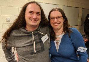Joey and Angela standing together and smiling, Joey wearing a grey hoodie with a black 'there exists' symbol, and a nametag saying Joey, and Angela wearing a blue dress with a sparkly neckline that looks like a 'for all' symbol, and a nametag saying Angela.