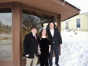 Byron wearing a black hat, black jacket with white shirt and red tie, and khaki pants, me wearing a long black dress and a tiara, and Joey wearing a black suit with a white shirt, all standing in front of a giant twine ball, seen through the glass of a pagoda. There is much snow on the ground.