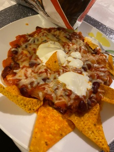 An orange mixture with some beans visible, covered in grated cheese and a few dollops of sour cream, all on a white plate with some triangular corn chips, on top of a sparkly place mat. The corn chip bag is nearby.