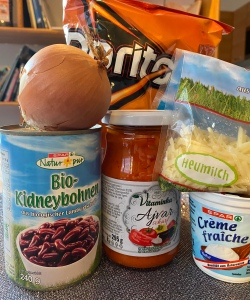 A bag of Doritos behind a can of kidney beans, a jar of Ajvar, some crème fraîche, a bag of grated cheese, and an onion.